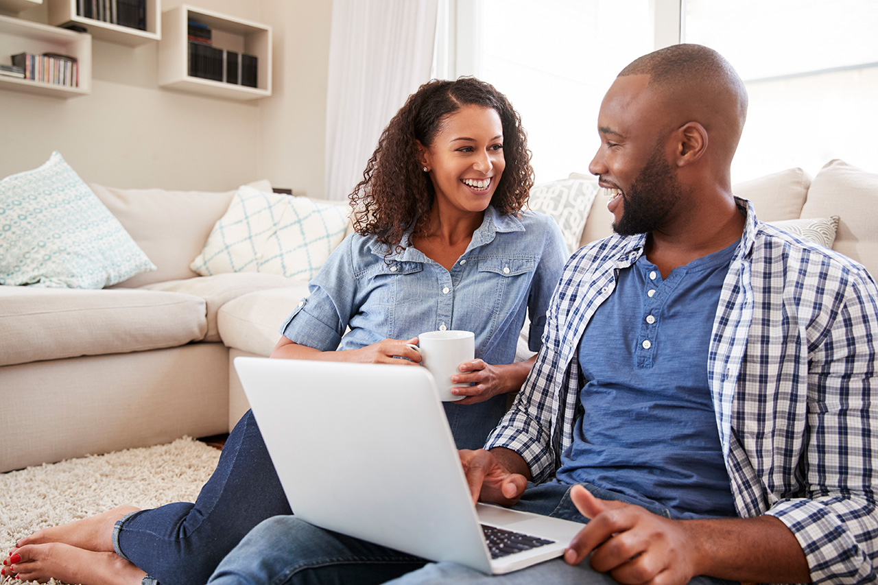 Young black couple using laptop